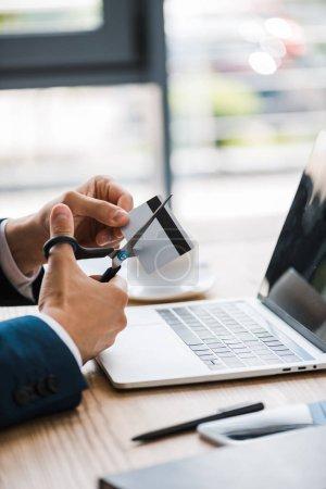 Photo pour Vue recadrée de l'homme tenant des ciseaux près de la carte de crédit et gadgets sur le bureau - image libre de droit