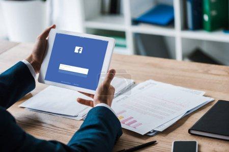 kyiv, Ukraine - 8. Juli 2019: Ausgeschnittene Ansicht eines Mannes, der ein digitales Tablet mit Facebook auf dem Bildschirm in der Nähe von Diagrammen und Diagrammen hält