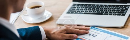 Photo for Panoramic shot of man near paper with credit report letters and cup of coffee - Royalty Free Image