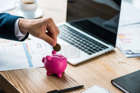 cropped view of businessman putting coin into pink piggy bank near laptop and cup with coffee