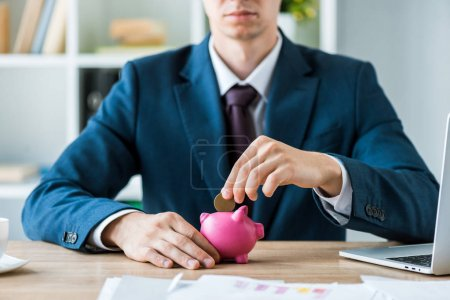 cropped view of businessman putting metallic coin into pink piggy bank