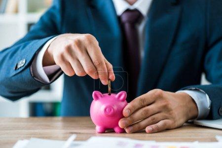 selective focus of man putting metallic coin into piggy bank near laptop