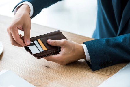 cropped view of businessman touching credit card while holding wallet
