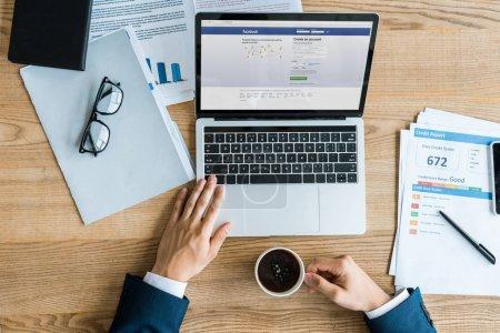 kyiv, Ukraine - 8. Juli 2019: Draufsicht des Geschäftsmannes, der Tasse in der Nähe des Laptops hält, mit Facebook-Website auf dem Bildschirm
