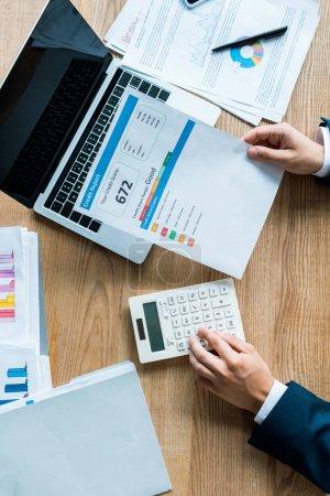 Photo pour Vue du dessus de l'homme d'affaires détenant le document avec des lettres près de la calculatrice et ordinateur portable - image libre de droit