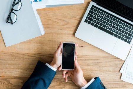 Photo pour Vue de dessus de l'homme tenant smartphone avec écran vide près de l'ordinateur portable et des lunettes sur la table - image libre de droit