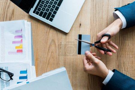 Photo pour Vue supérieure de la carte de crédit de coupe d'homme avec des ciseaux près de l'ordinateur portatif - image libre de droit