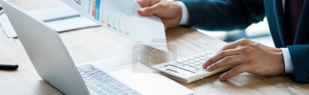 Photo for Panoramic shot of man holding paper with lettering and counting on calculator - Royalty Free Image