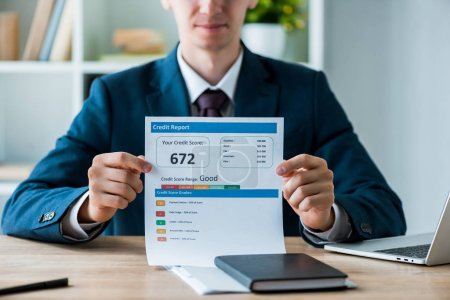 Photo for Selective focus of man holding document with credit report lettering near laptop in office - Royalty Free Image