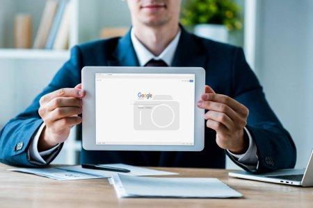Photo pour Kiev, Ukraine - 8 juillet 2019: focus sélectif de l'homme tenant tablette numérique avec application Google sur l'écran près de l'ordinateur portable dans le bureau - image libre de droit