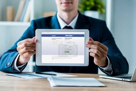 kyiv, Ukraine - 8. Juli 2019: selektiver Fokus des Mannes mit digitalem Tablet und Facebook-App auf dem Bildschirm in der Nähe des Laptops im Büro