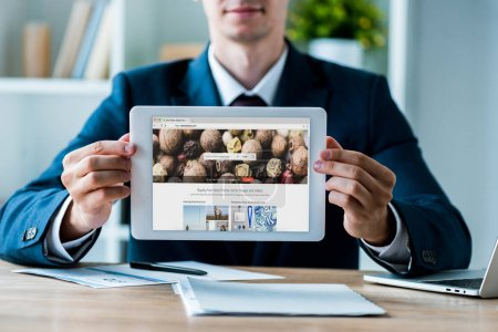 Photo for KYIV, UKRAINE - JULY 8, 2019: selective focus of man holding digital tablet with depositphotos app on screen near laptop in office - Royalty Free Image