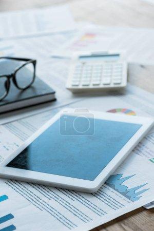 Photo pour Mise au point sélective de la tablette numérique près de l'ordinateur portable et des lunettes sur les papiers - image libre de droit