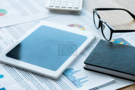 Photo for Selective focus of digital tablet near notebook and glasses on documents - Royalty Free Image