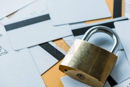 selective focus of metallic padlock near credit cards