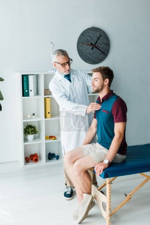 bearded chiropractor in white coat and glasses touching back of patient with closed eyes