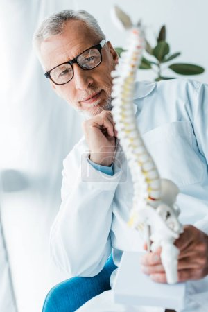 Photo for Selective focus of happy doctor in white coat and glasses holding spine model in clinic - Royalty Free Image