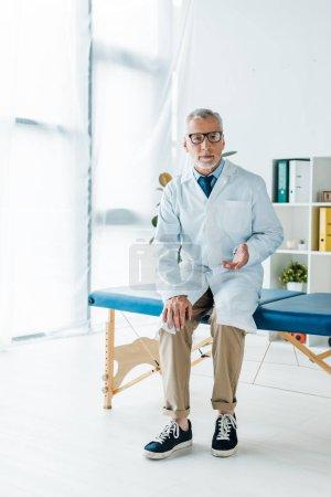 Photo pour Docteur barbu en lunettes et manteau blanc assis sur la table de massage et gestuelle à la clinique - image libre de droit