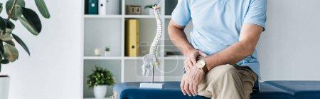 Photo pour Tir panoramique de l'homme s'asseyant sur la table de massage près du modèle de colonne vertébrale - image libre de droit