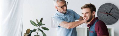 Photo for Panoramic shot of bearded man in glasses touching patient with pain in clinic - Royalty Free Image
