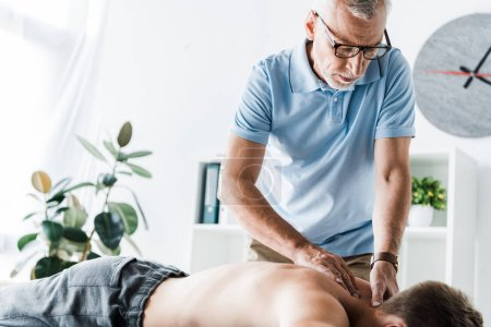 Photo pour Chiropraticien barbu faisant massage au patient sur la table de massage - image libre de droit