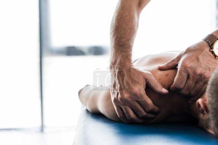 Photo pour Vue recadrée du chiropraticien faisant massage au patient torse nu - image libre de droit