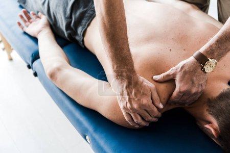 Photo pour Vue recadrée du chiropraticien faisant massage à l'homme torse nu - image libre de droit