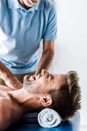 Photo pour Vue recadrée du chiropraticien barbu faisant massage à l'homme avec douleur - image libre de droit