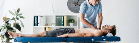 Photo pour Plan panoramique de chiropracteur barbu faisant massage à l'homme sur la table de massage - image libre de droit