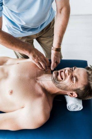 Photo pour Vue aérienne du chiropraticien faisant massage à l'homme les yeux fermés souffrant de douleur - image libre de droit