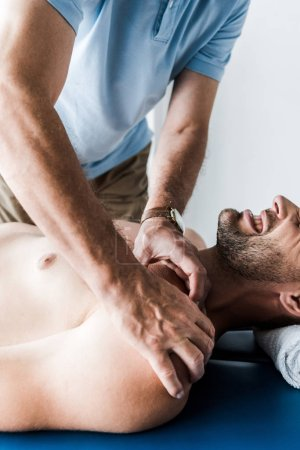 Foto de Vista recortada del quiropráctico haciendo masaje al hombre con los ojos cerrados sufriendo dolor - Imagen libre de derechos