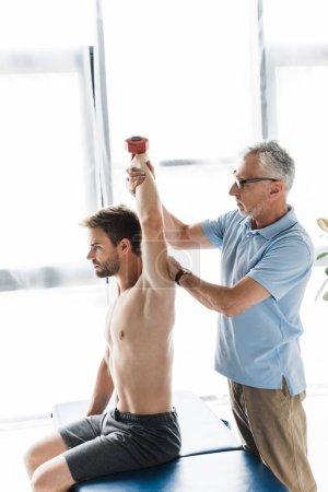 Photo pour Chiropraticien dans des lunettes debout près de l'homme torse nu faisant de l'exercice avec haltère en clinique - image libre de droit