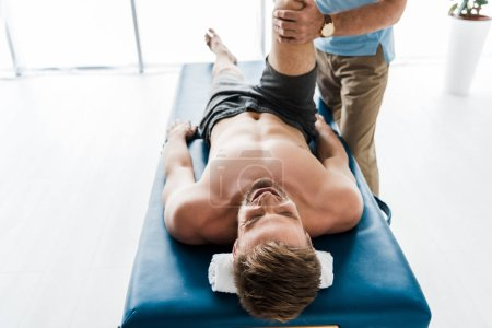 Photo pour Vue recadrée du médecin près du patient couché sur la table de massage et s'entraînant à la clinique - image libre de droit