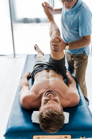 Photo pour Vue recadrée du médecin près du patient avec les yeux fermés couché sur la table de massage et de l'exercice à la clinique - image libre de droit