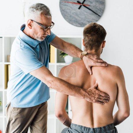 Photo pour Médecin barbu dans des lunettes touchant le dos d'un patient torse nu à la clinique - image libre de droit