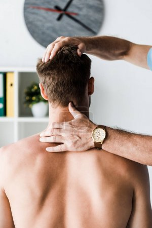 Photo for Cropped view of doctor touching neck of muscular patient sitting in clinic - Royalty Free Image