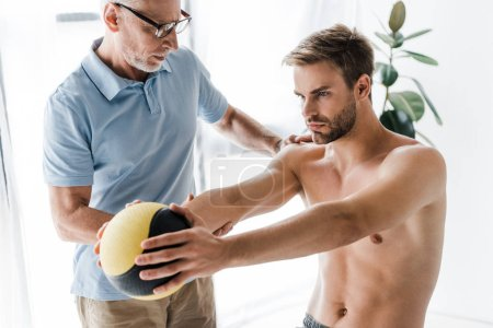 bearded doctor in glasses looking at shirtless patient working out with ball