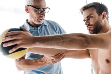 Photo for Selective focus of doctor in glasses looking at shirtless patient working out with ball - Royalty Free Image