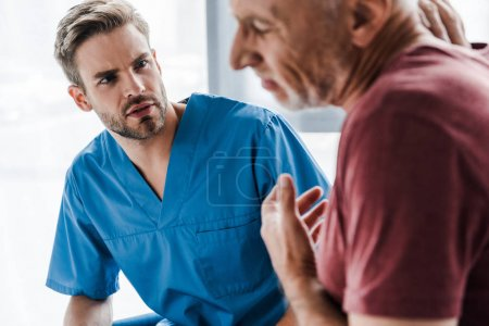 Photo for Selective focus of handsome doctor looking at man in clinic - Royalty Free Image