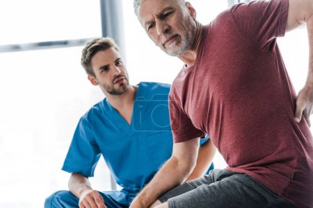 Photo for Selective focus of man suffering from pain near doctor in clinic - Royalty Free Image