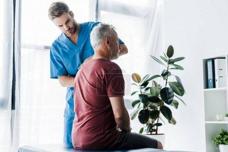Photo pour Chiropraticien beau debout près du patient mature - image libre de droit