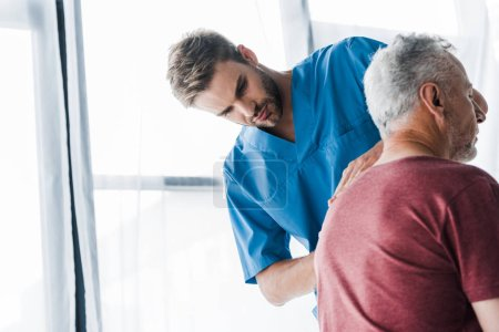 Photo for Handsome chiropractor looking at back of mature patient - Royalty Free Image