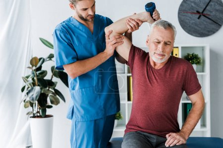 Photo pour Homme d'âge moyen faisant de l'exercice avec haltère près du médecin en clinique - image libre de droit