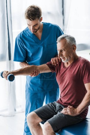 Photo pour Docteur restant près de l'homme mûr s'exerçant avec l'haltère dans la clinique - image libre de droit