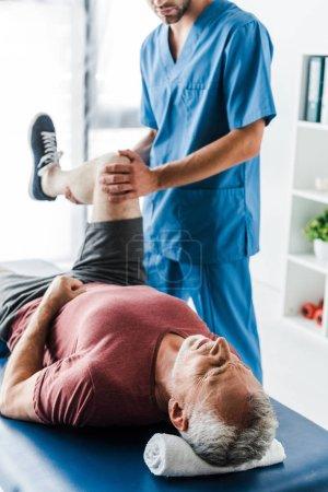 Photo pour Vue recadrée du docteur touchant la jambe de l'homme mûr travaillant dehors sur la table de massage - image libre de droit