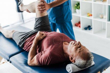 Foto de Vista recortada del médico tocando la pierna del hombre maduro entrenamiento en la mesa de masaje - Imagen libre de derechos