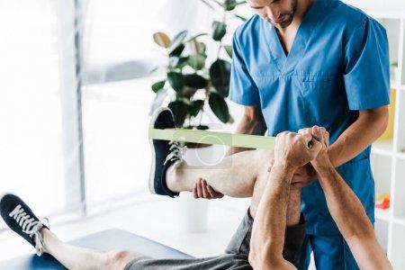 Photo pour Vue recadrée du médecin tenant la jambe sur la formation de l'homme mature avec des sangles de suspension - image libre de droit