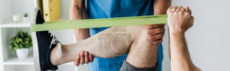 Foto de Disparo panorámico del médico cerca del hombre haciendo ejercicio con correas de suspensión - Imagen libre de derechos