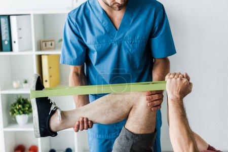 Photo pour Vue recadrée du docteur barbu retenant la jambe de l'homme mûr s'exerçant avec des élastiques - image libre de droit