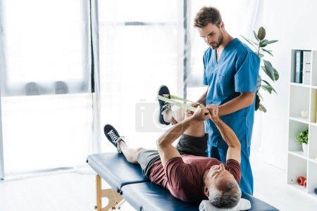 Foto de Guapo médico barbudo sosteniendo pierna de paciente maduro haciendo ejercicio con elásticos - Imagen libre de derechos